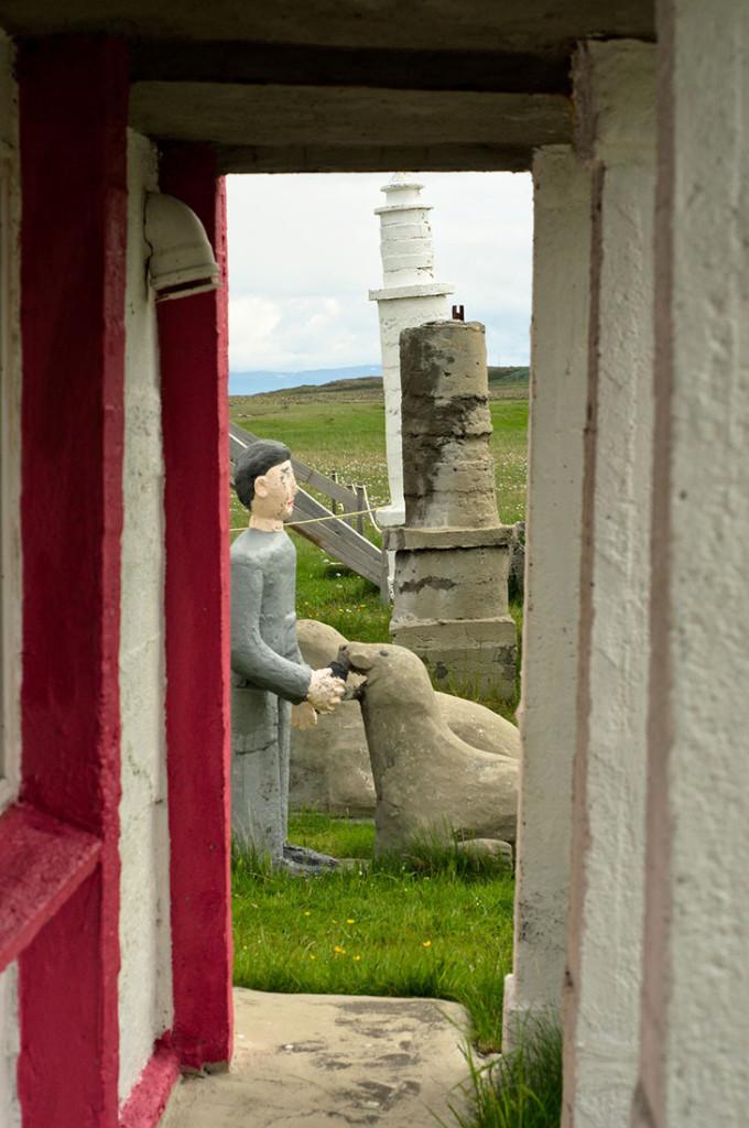 Estátuas em Selárdalur vistas através da arcada de um edifício