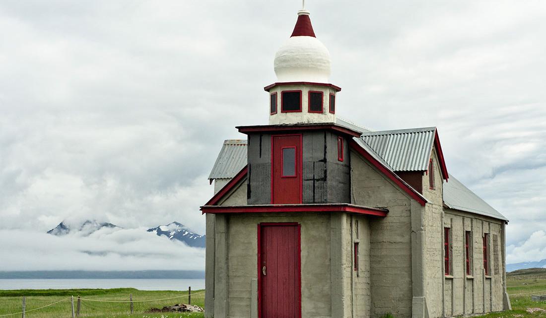 capela em betão com cúpula branca e pormenores vermelhos construída por Samúel Jónsson em Selardalur