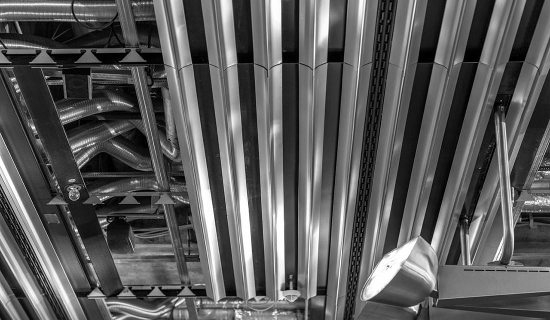 Tubagens e calhas metálicas num tecto de um aeroporto