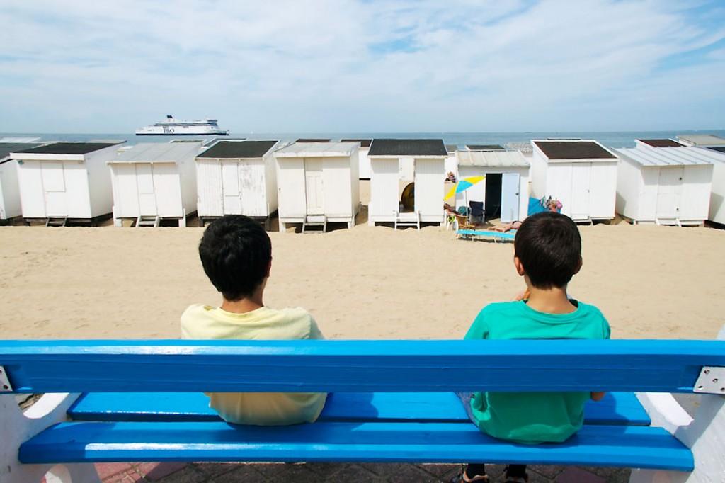 Crianças sentadas num banco junto à praia em Calais.