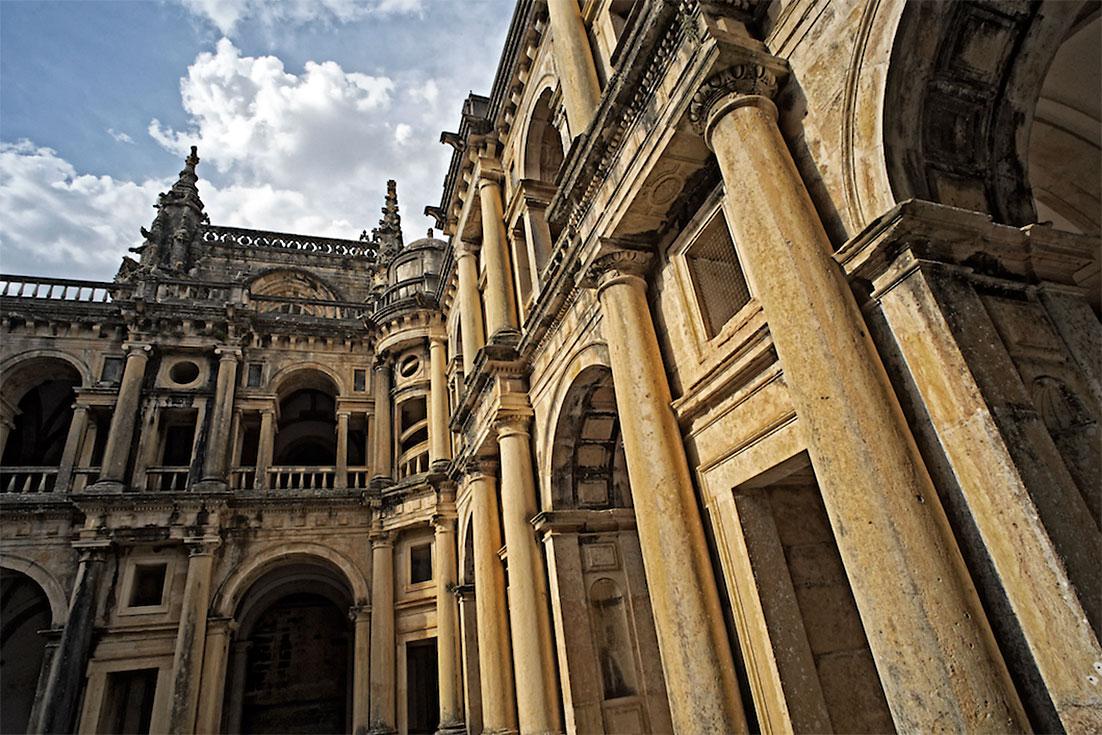 Fachada com grandes colunas de pedra no claustro principal do Convento de Cristo