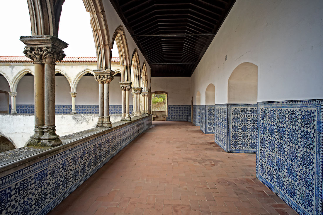 Corredores com paredes forradas a azulejo que ladeiam o primeiro piso de um dos claustros