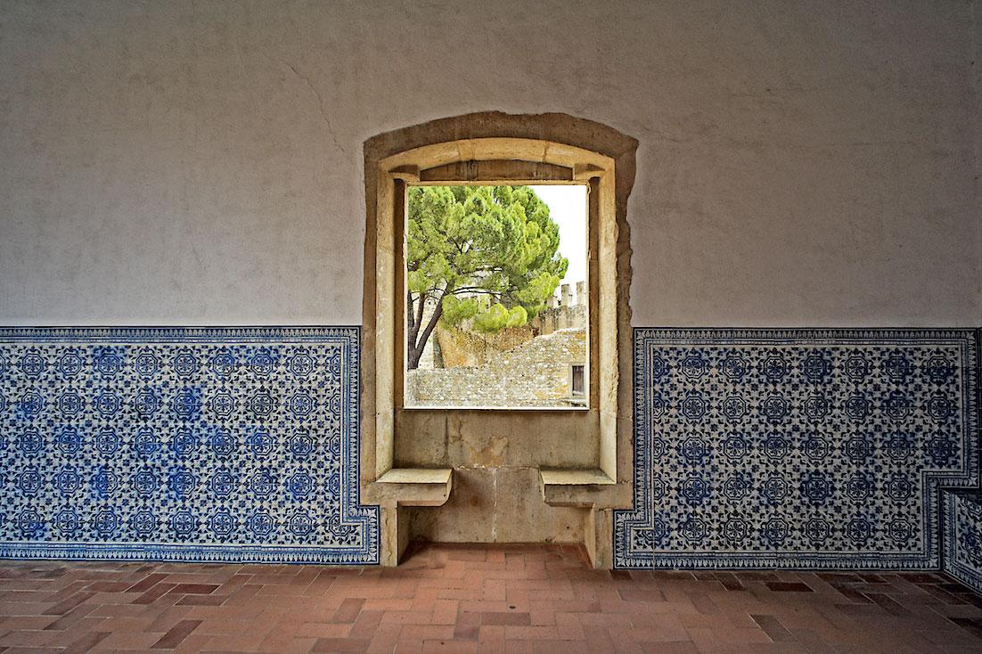 Sala decorada com azulejos com janela que dá para um jardim do Convento de Cristo