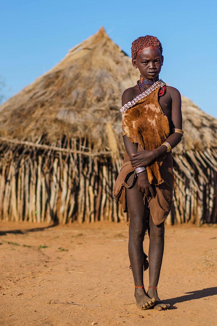 menina hammer junto a uma casa de palha da sua aldeia