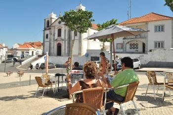 Pessoas numa esplanada junto à igreja em Palmela.