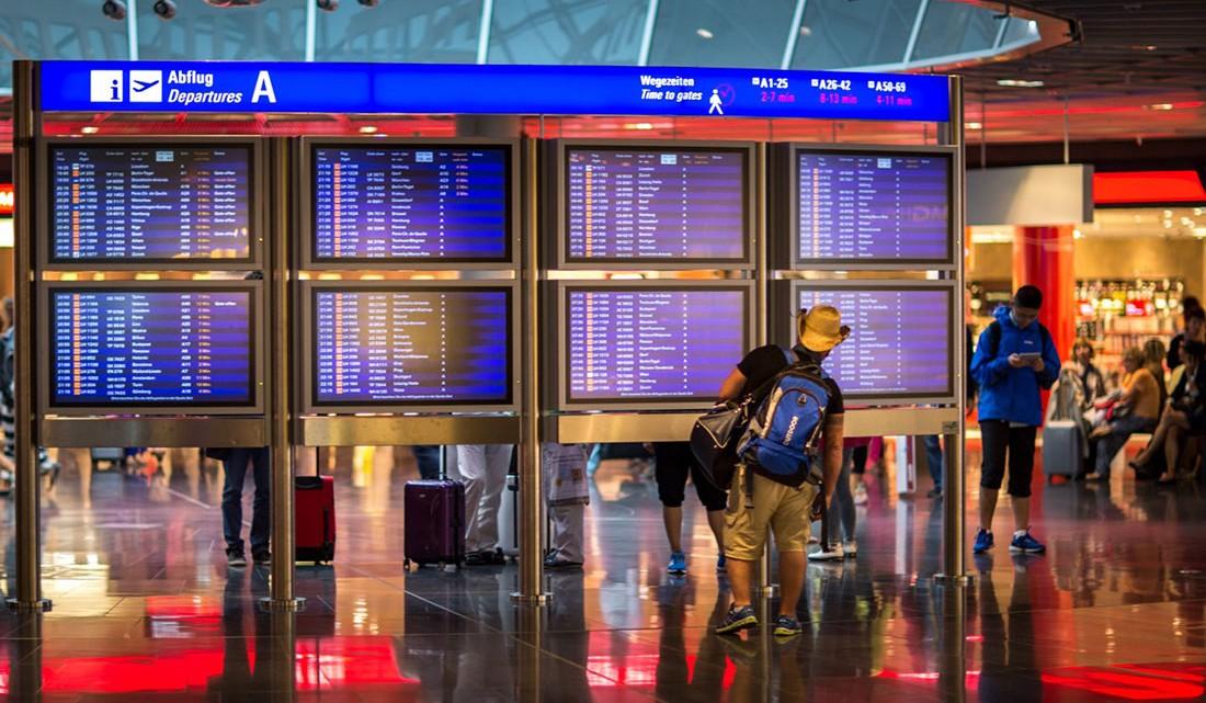 passageiro a observar painéis com horários dos voos de partida num aeroporto