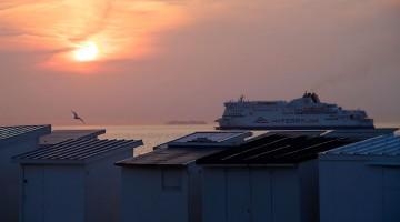 ferry e barracas de praia ao pôr-do-sol na cidade de Calais, em França.