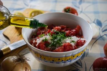 Regando salada israelita de pepino e tomate com azeite virgem dourado.