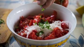 Mão a espalhar salsa picada sobre salada israelita de pepino e tomate dentro de uma saladeira branca e dourada.