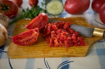 Tomate de cores vivas picado sobre tábua de madeira rodeado de legumes