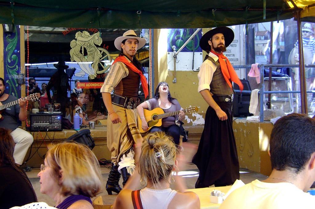 Grupo de dançarinos e músicos que actuam para o público num bar del Caminito em Buenos Aires