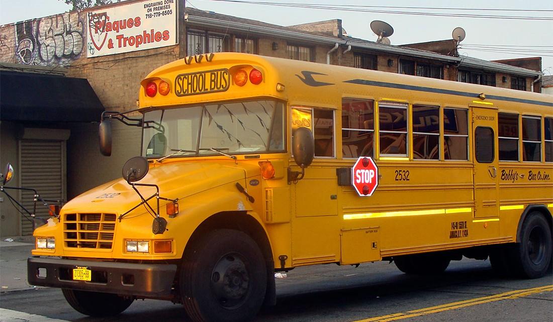 tipico autocarro escolar americano, em cor amarelo forte, junto à avenida 51 em Queens