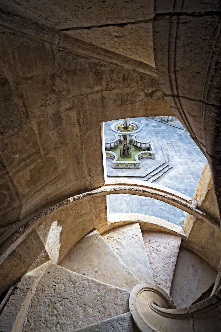 escada em caracol de onde se avista a fonte central do claustro principal do Convento de Cristo.