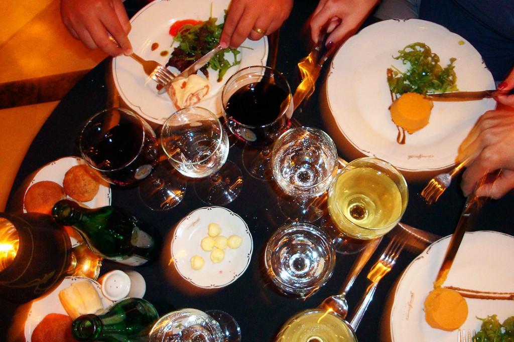 vários pratos com alimentos e copos com bebidas numa mesa de jantar