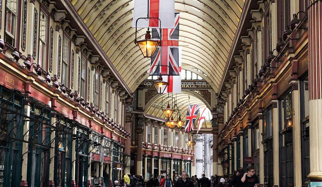 pessoas e bandeiras numa das galerias do Leadenhall Market em Londres