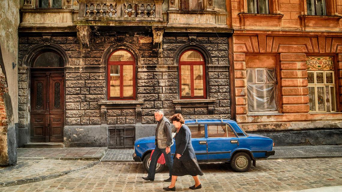 Casal a caminhar numa rua antiga de Lviv com Trabant azul estacionado