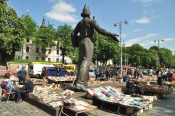 Feirinha de livros e antiguidades instalada junto a grande estátua numa praça de Lviv