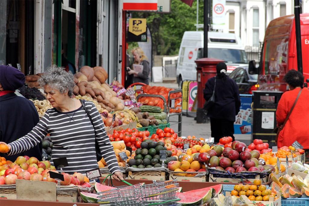 mulher a escolher fruta num mercado de rua em Londres
