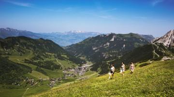 mulheres num trekking nas montanhas do liechtenstein, com vista para uma aldeia no vale