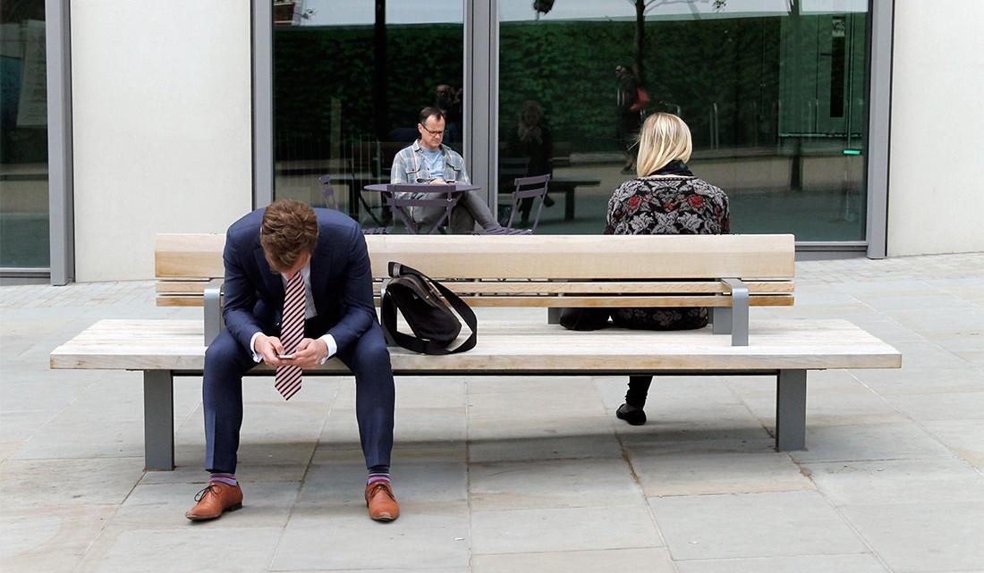 pessoas sentadas num banco de rua em Londres