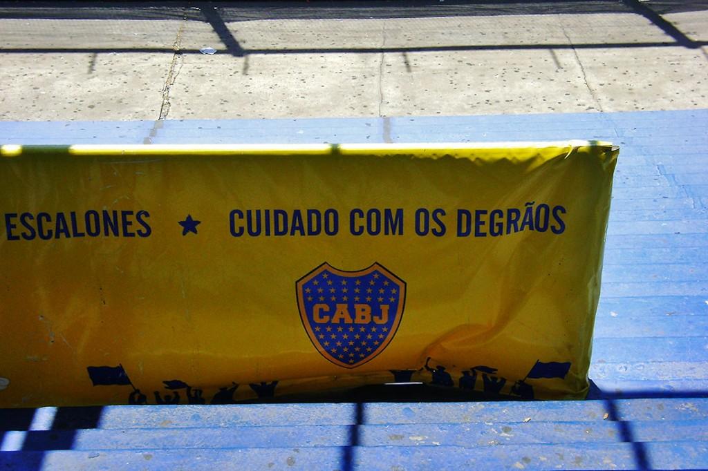 placard amarelo instalado nas escadas das bancadas do estádio La Boca em Buenos Aires