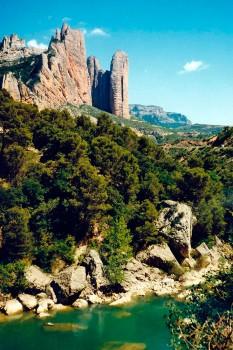 Rio Gállego envolvido por vegetação densa e os Mallos de Riglos