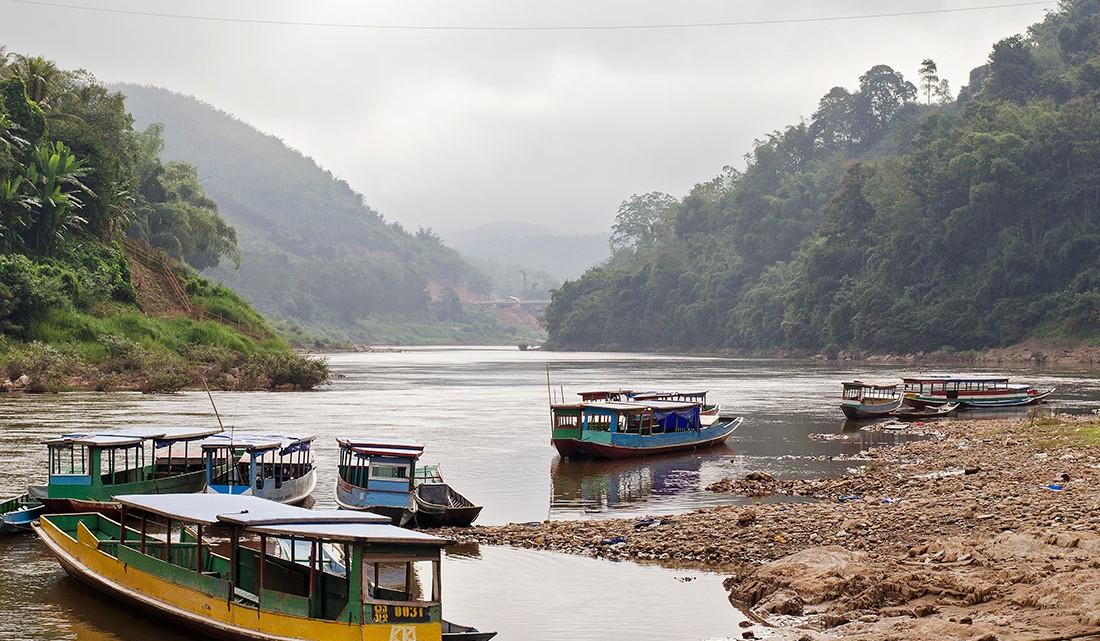 Barcos com várias cores na margem do rio Nam Ou, junto à aldeia Muang Ngoi Neua, no Laos.