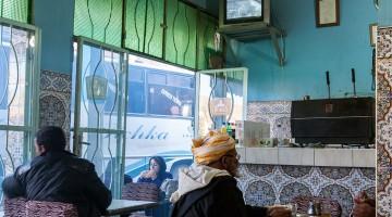Pessoas num café central de paredes revestidas a azulejo algures na estada que atravessa o Atlas marroquino.