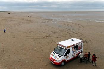 Carrinha de venda de gelados sobre as areias da praia de Southport.