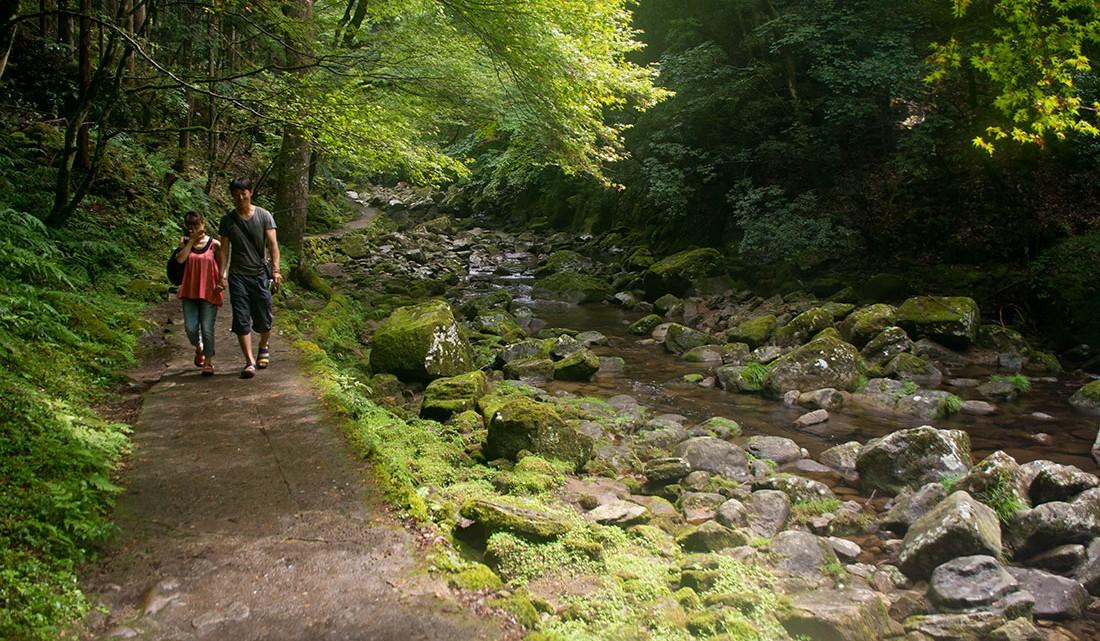 Casal de jovens a caminhar junto ao rio akame‐cho.