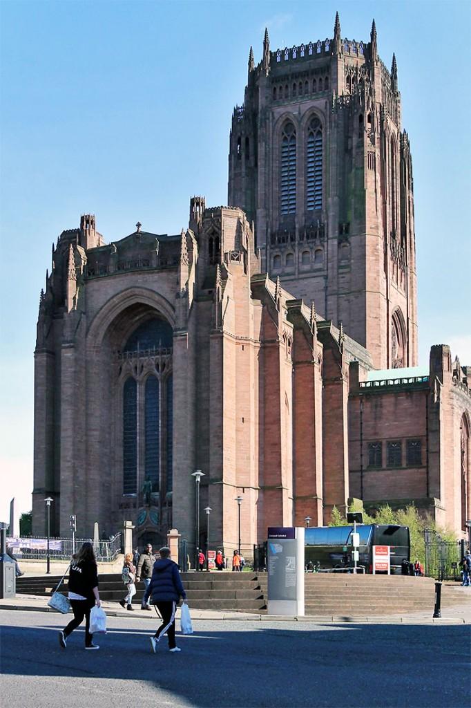 Pessoas que caminham frente à grande catedral de Liverpool.