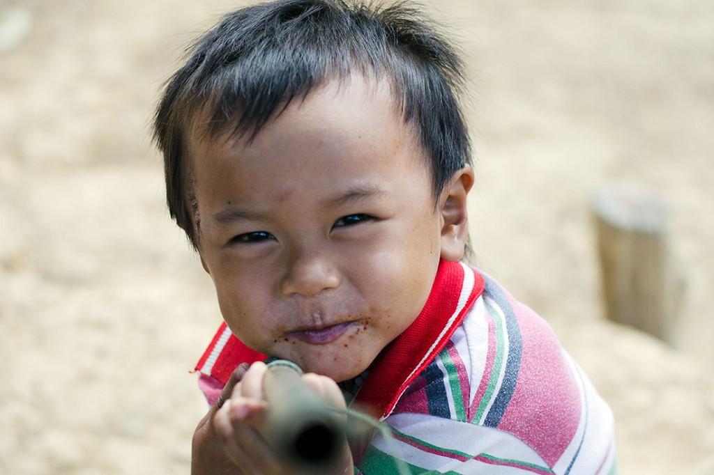 Criança a brincar com cana na aldeia de Muang Nngoi Neua.