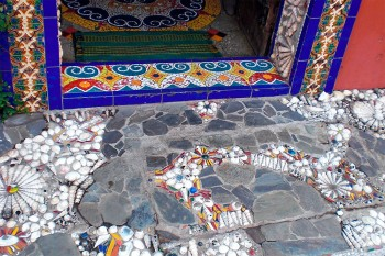 Mosaicos, azulejos e conchas no pavimento de entrada do Hotel Venite em Goa.