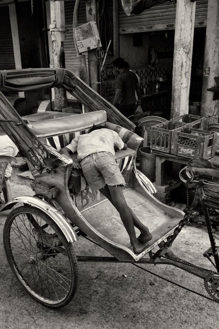 homem a dormir sobre o seu rickshaw