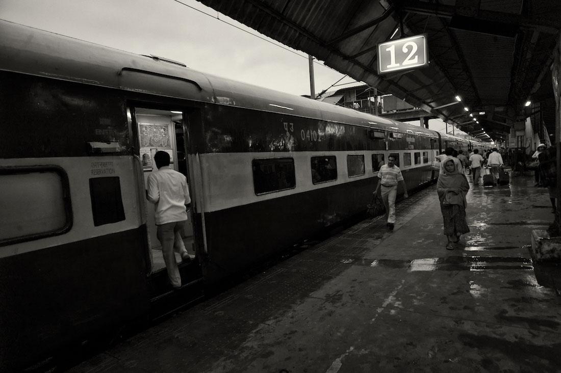 Homem a entrar no comboio estacionado no cais 12 da estação de Nova Delhi.