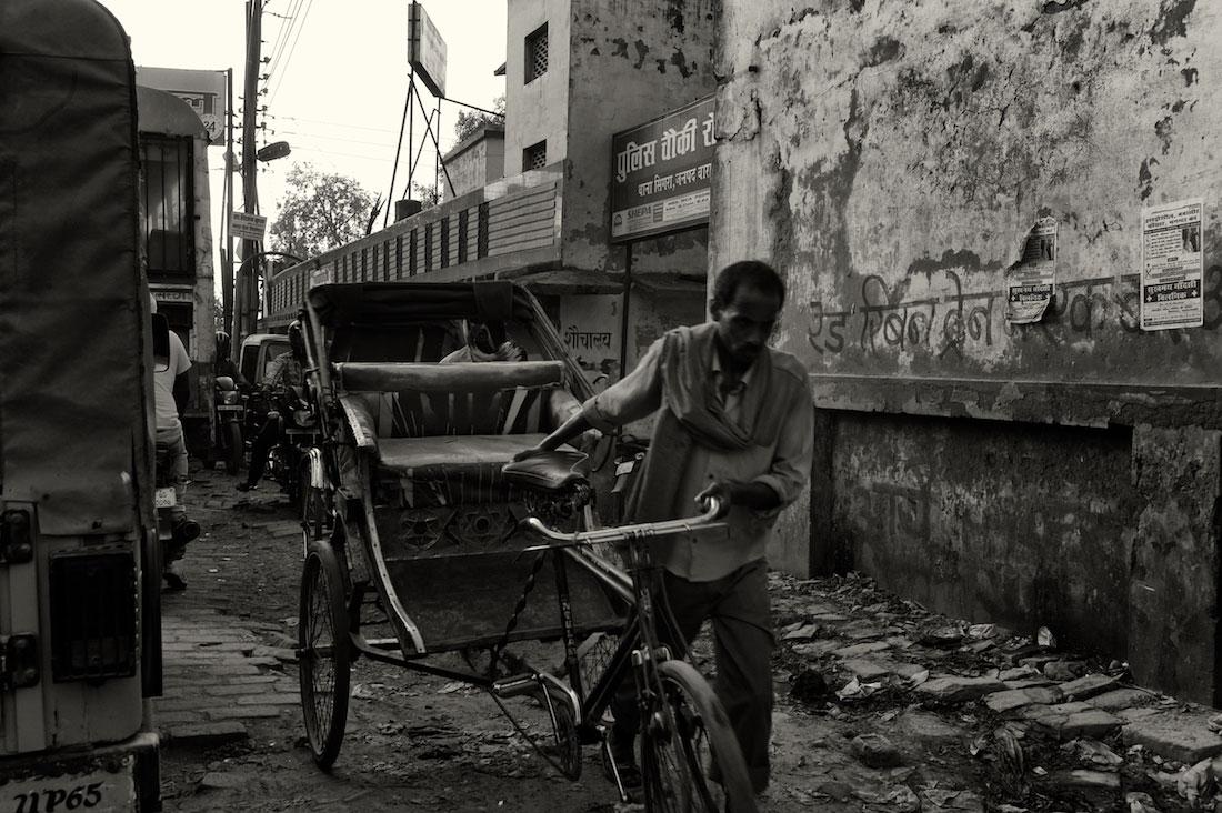 Homem a puxar rickshaw versão bicicleta na Índia.