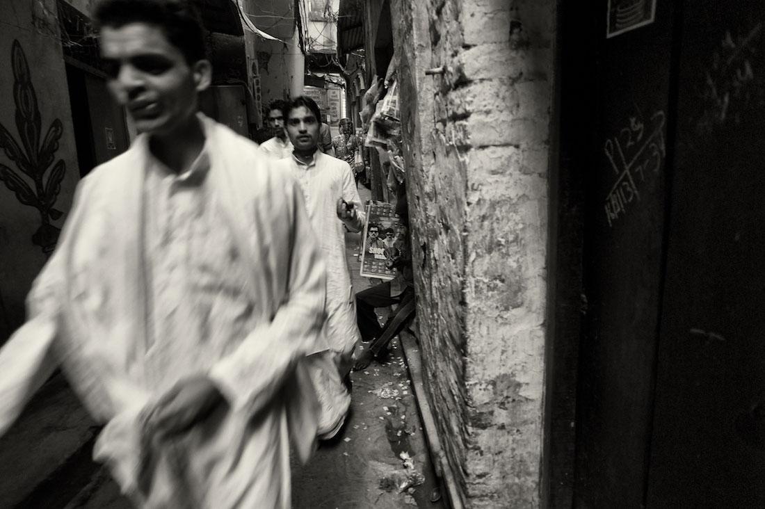 Homens vestidos de branco que passam numa ruela muito estreita de Varanasi antiga.