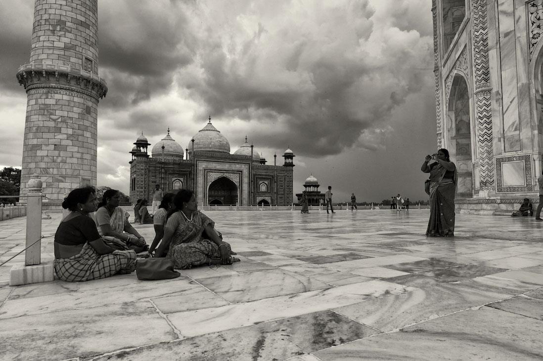 Grupo de mulheres indianas a fotografarem-se junto ao Taj Mahal.