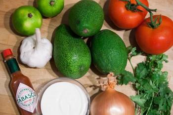 Abacate, cebola, tomate, alho, coentros, nata e tabasco utilizados na preparação do guacamole.