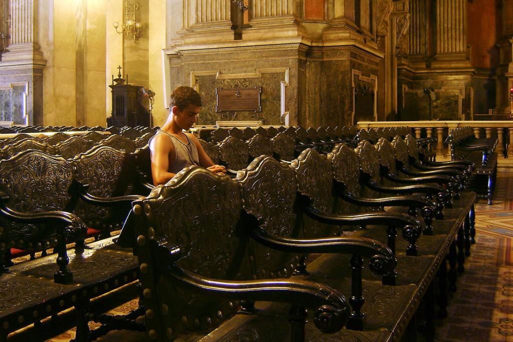 Rapaz sentado nos grandes cadeirões do interior da igreja da candelária no Rio de Janeiro.