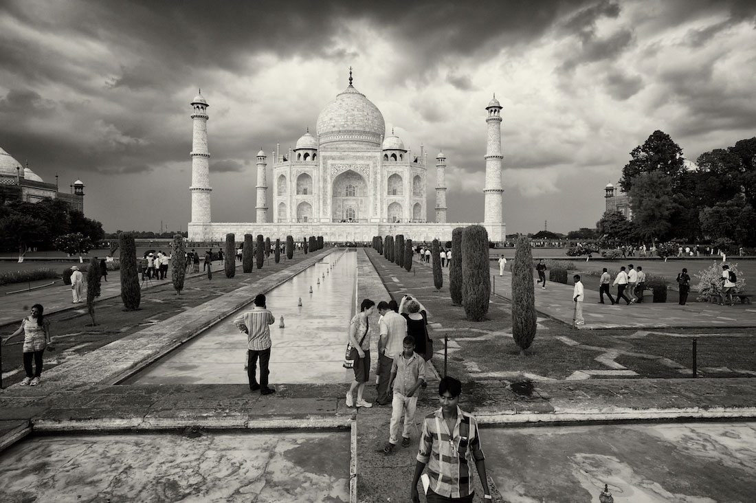 Pessoas nos Jardins frontais com fontes no recinto do Taj Mahal em Agra.