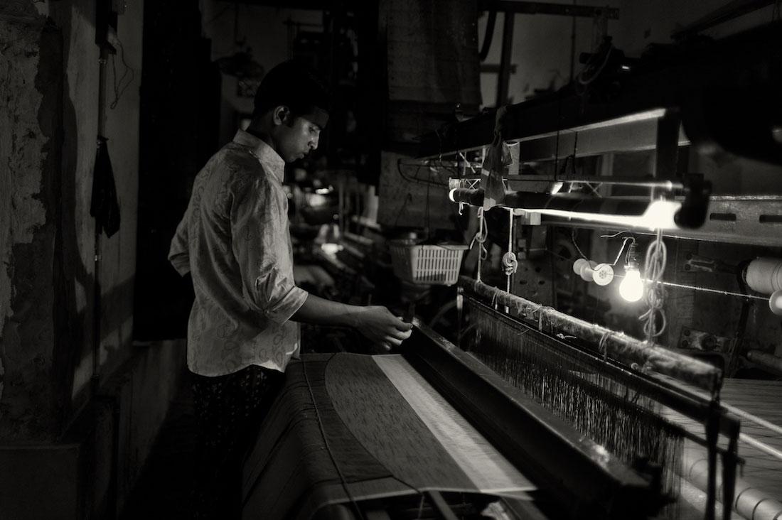 Rapaz a trabalhar com um tear numa pequena fábrica de tecidos em Varanasi.