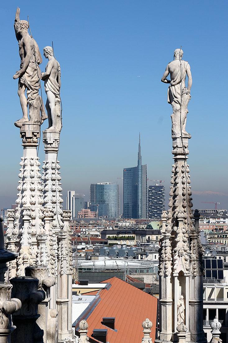 Edifícios modernos da cidade de Milão por entre as esculturas do terraço da catedral Duomo