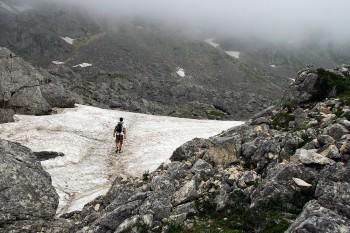 Montanhista a caminhar sobre o glaciar no parque nacional de Durmitor no Montenegro.
