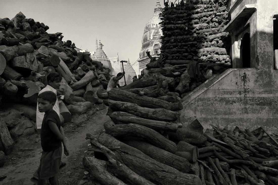 Crianças junto a montes de madeira para usar nas piras funerárias de Varanasi.