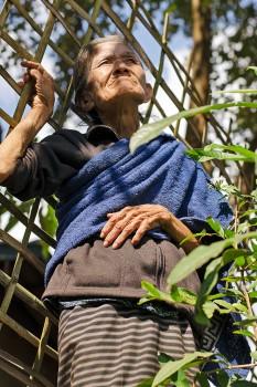 Mulher idosa junto a vedação de madeira na aldeia de Muang Ngoi Neua.