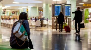 Viajante sentado num sofá e passageiros a olhar os painéis de informação do Aeroporto de Lisboa.