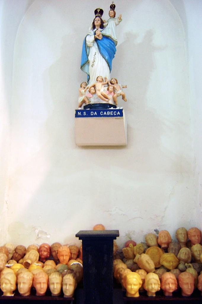Imagem de Nossa Senhora da Cabeça junto a muitas cabeças em cera.