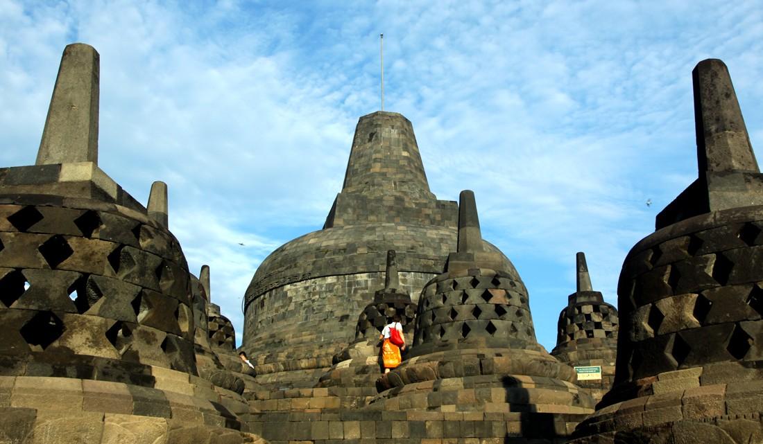 No topo do Templo de Borobudur um turista passeia no meio das estupas
