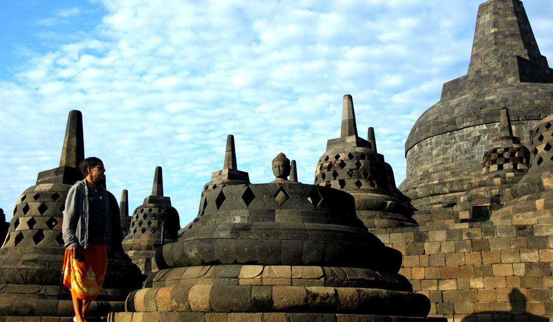 Mulher junto a uma das múltiplas estátuas de Buda existentes no topo do templo Borobudur
